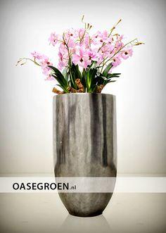 Zilveren vaas gevuld met frisse roze kunstbloemen; Een kleurrijk en vrolijk object in elk interieur