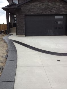 Standard broom driveway with stamped border design in black using stone skin texture stamp