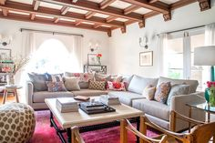 Bohemian living room with neutral sofa, vibrant pillows, and exposed ceiling beams