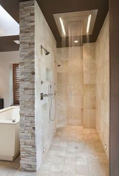 My favorite shower I've ever seen. Tub in front of rock wall, open on both sides, rain fall shower head with regular shower heads as well. Perfect