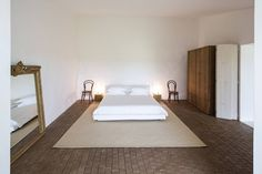A jute rug, Softball Bed by Piero Lissoni, Thonet chairs, and a custom wardrobe in one of the guest bedrooms.