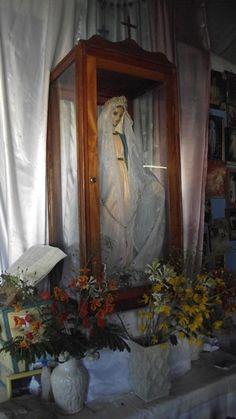Oratório em madeira com laterais em vidro transparente, acondicionando imagem sacra de nossa senhora, ornado com vasos de flores amarelas nas laterais.
