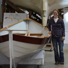 Boatbuilder Jodi Carpenter standing alongside Blue Pike. In the background, Porcupine, eagerly awaits her launch exactly 11 months from today.