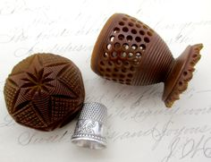 Antique Victorian Carved Tagua Nut (Vegetable Ivory) Thimble / Spool Holder with Sterling Silver Ketcham & McDougall Thimble. The carved nut has an ornate design with little holes on the sides. I thin