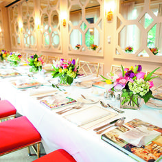 To create that effect, a single long table was topped with white linens and vibrant centerpieces of hydrangeas, tulips, and lilies arranged in square glass vessels. Taylor Lord Photography