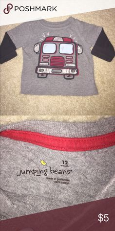 """Boys 12 Months Firetruck Tee In excellent used condition Long Sleeved Tee. Gray with navy blue sleeves. Firetruck print on front. 100% cotton. Size 12 Months. By Jumping Beans.  *Don't like the price? Make your own using the """"make offer"""" button! I also offer awesome discounts on bundles! Add more than one item from my closet to a bundle, and I will give you a private discounted offer!!!* Jumping Beans Shirts & Tops Tees - Short Sleeve"""