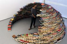 """Just one grab, and this thing will topple. Colombian artist, Miler Lagos, created this """"semi book igloo,"""" titled Home, in an installation in 2011 at MagnanMetz Gallery in New York. No glue, nothing holding the books together, just neatly and perfectly stacked so as not to fall over on itself. And with a name like Home, it feels very comforting if you want to read The Hunger Games trilogy amongst other novels."""