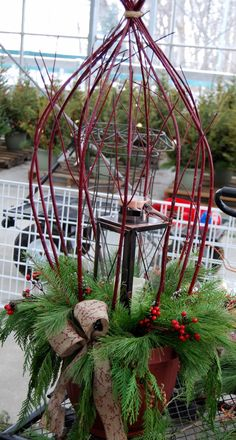 Incorporate an outdoor lantern with LED candle in an outdoor pot. Red Twigged dogwood is simply tied at the top.