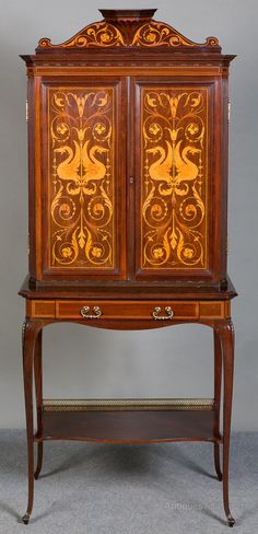 A superb Arts  Crafts inlaid cabinet on stand from the renowned workshop of Shapland and Petter. Constructed from top quality mahogany, this cabinet has 2 panelled doors which are profusely inlaid with griffins,scrolls and foliage in satinwood, boxwood and various stained woods. The interior with various shelves and compartments, the bottom shelf slides out and is adjustable