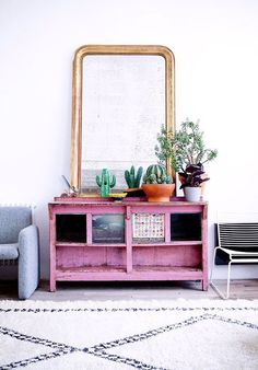 This cute little corner is what my dreams are made of. Pink cabinet with open shelves and potted plants on top. Oh, and a huge mirror with copper frame!