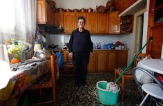 """Voula Stamatakos, 72, a housewife, poses for a picture in her home in the village of Krokeae, Greece, on March 18, 2012. When asked how she had been affected by the economic crisis, Stamatakos replied, """"My pension has been cut but I try to stay positive."""""""