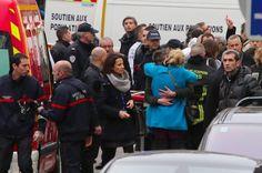 12 Dead in Shooting at French Satirical Newspaper - People hug each other outside the French satirical newspaper Charlie Hebdo's office, in Paris, Wednesday, Jan. 7, 2015. (Image source: AP/Remy de la Mauviniere)