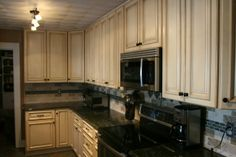 Glazed antique white kitchen cabinets with black appliances   Furniture Kitchen ~ Antique White Cabinets For Your Lovely Kitchen ...