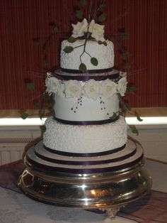 My Sister and i made this Wedding cake, with sugar roses and leaves, and cadbury purple ribbon and beads :)