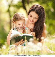 idea: mom and daughter reading a christmas book by the christmas tree