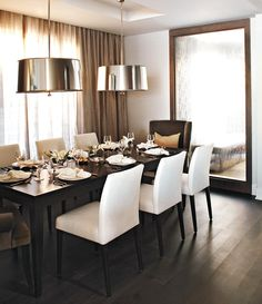 Simple table, simple chairs, simple curtains, simple light fixtures, dramatic mirror.