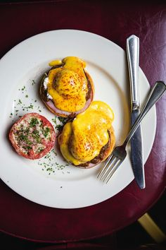 Brennan Eggs Hussarde is a savory take on the traditional Eggs Benedict with a rich wine sauce, ham, mushrooms, tomato and Canadian bacon.