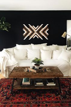 Brighten up a dark statement wall color with wood artwork. A vintage rug and well-worn wood coffee table give this living room a boho style. Photo by Boys Bedroom Furniture, Living Room Furniture, Living Room Decor, Furniture Ideas, Living Rooms, Wood Artwork, Statement Wall, Furniture Arrangement, Wall Colors