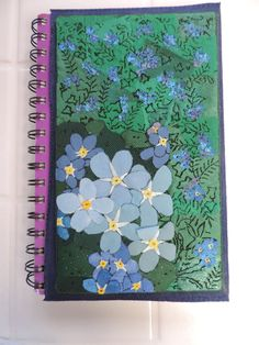 A forget-me-not slipcover for a weekly planner that can be reused. Created with a soldering iron.