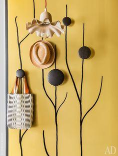 Стена прихожей с нарисованными деревцами. Вешалки The Dots, Muuto. Абажур из папье-маше Egg of Columbus, Seletti.