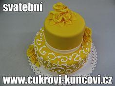 žlutý svatební dort s bílým zdobením