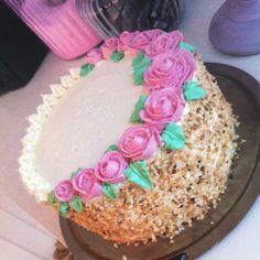 Tårta fylld med glasscreme och blåbärsggrädde. Spacklad med citronsmörkräm och dekorerad med spritsade rosor samt hasselnötter.