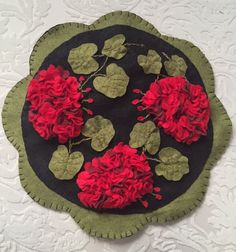 "Barb from Pa Stitched this ""Geraniums"". Pattern for Geraniums can be found here: http://cathspenniesdesigns.com/item_170/Geranium-Beauty-Wool-Applique-Penny-Rug-Candle-Mat-Pattern.php"