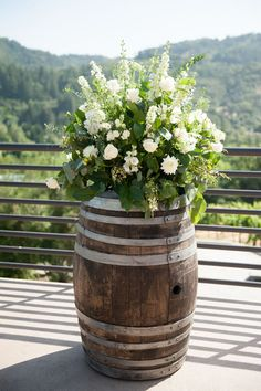 Rustic wine barrel topped with a gardeny arrangement of white roses and stock. Sage and White Vineyard Wedding  // Sbragia Family Vineyards, a Milestone property | Jennifer Bagwell Photography