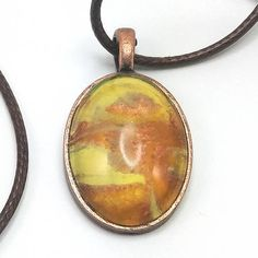 Every piece of jewelry is a one of a kind handmade work of art. The jewelry is made by mounting a tiny section of a painting in a pendant so every piece is original. Its like wearing a tiny unique painting around your neck. This one of a kind handmade Pour Paint Pendant is part of the