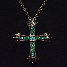 Stunning cross in genuine emerald green crystal Stunning cross in shimmering genuine emerald green Austrian crystal set in simulated dark silver / charcoal gray. THE ICING Jewelry Necklaces