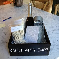 Decorative box with champagne, chocolate covered pretzels, sparkling water and a note.
