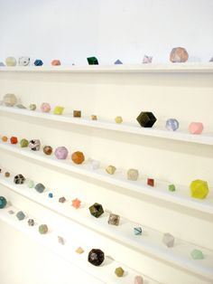 Shelves of small sculptural objects, like a curated collection of odd rocks/minerals (Lydia Shirreff)