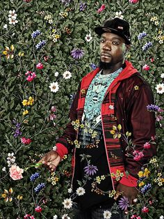 African American artist Kehinde Wiley with his signature floral yet wallpaper background.