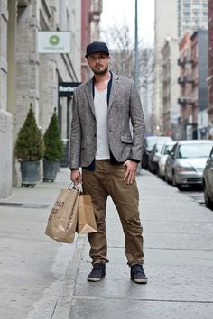 Try pairing a grey wool blazer with brown chinos for a work-approved look. Complement this look with charcoal canvas boots.  Shop this look for $171:  http://lookastic.com/men/looks/baseball-cap-boots-chinos-cardigan-crew-neck-t-shirt-blazer/5782  — Navy Baseball Cap  — Charcoal Canvas Boots  — Brown Chinos  — Navy Cardigan  — White Crew-neck T-shirt  — Grey Wool Blazer