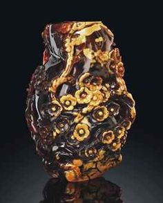 A CARVED AMBER 'PRUNUS' VASE   18TH/19TH CENTURY   The vase is carved in relief with gnarled branches of flowering prunus around the exterior. Each five-petalled bloom is detailed with incised stamens. The mottled amber is of dark brown and light caramel tones.  6 5/8 in. (17 cm.) high, wood stand
