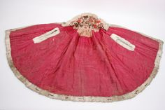 Capet consists of four main parts and two wedges on each side. Large wide collar that is sewn on with pleats  around the neck. The garment has fur trim on all edges and in ermåpningene. Small metallhempe throat. Lined with floral fabric.  MATERIALS Cotton - fodder, Rabbit - with sewn brown fur pieces Lin - fibers, quilted COLOR Red (Outer shell), white with brown small pieces (fur trim), white, brown, red (feed 1 with printed flowers) Naturhvir and light brown