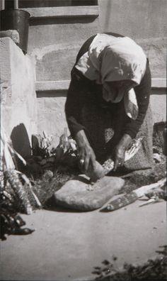Photograph of Luiseno woman, 1927-1936. Handwritten caption on verso: SHELLING CORN ON METATE/ LUISENA/ S. CALIF./ (WHO?). Subjects: portraits, California Indians, Luiseno, Pala Reservation, women, food preparation, corn