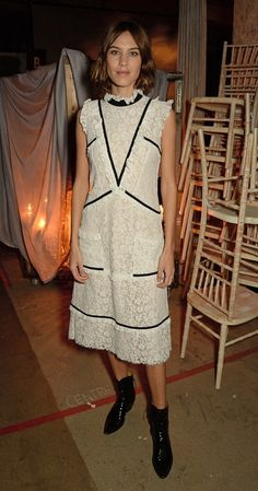 Alexa Chung wears a white lace Erdem midi dress with black detailing and cowboy boots