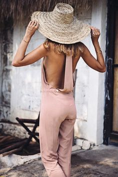 Try a soft pink open-back jumpsuit for vacay time. That straw hat is the perfect touch!