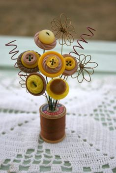 This sweet little bouquet made of vintage buttons is displayed in an small, old wooden spool with brown thread. It is only 4 inches tall. It