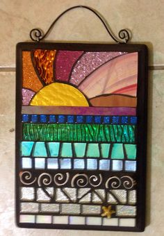 "This is an all hand cut, handmade mosaic Wall Hanging. It is a beach motif mosaic using stained glass, glitter glass, mirror glass and several other materials in a variety of colors. 6.5"" x 9.5"". It is grouted in Charcoal gray. The"