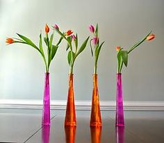 This set, sure to inspire dramatic modern art, consists of 2 hot pink and 2 vibrant orange tall tapered glass bottles. The small neck of each bottle lends itself to just one or two stems per vase.