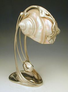 Moritz Haker Shell Desk Lamp.      Manufacturer Moritz Haker     Description Silver plate on pewter desk lamp with art nouveau floral decoration and a nautilus shell shade  Country of Manufacture Germany Date c.1900