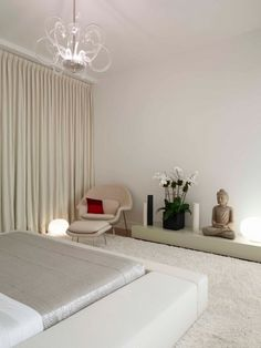 modern minimalist bedroom Asian decor white cream colors glass chandelier budha statue orchids