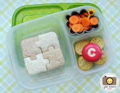 The larger section held a turkey bologna sandwich that was made into a puzzle using white and brown bread and my puzzle-shaped lunch punch. The other sections held a gray silicone muffin cup with sliced baby carrots and a giraffe pick and some mini crackers with a mini babybel cheese with the letter 'C' cut out of the wax using my mini metal alpahbet cutters.