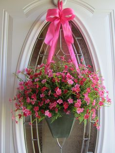 Beautifully arranged pink floral door wreath with a refurbished green vase that gives a garden field effect. Also added a pink wired ribbon for a finishing touch.