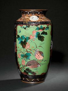A CLOISONNÉ VASE  MEIJI PERIOD (LATE 19TH CENTURY)  Worked in various thicknesses of gold and silver wire, coloured enamels and goldstone on a green ground with two panels of quail among wisteria and butterflies among magnolia, bordered by various floral and geometric designs, copper rims 30cm. high