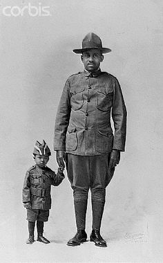 "ca. 1918, St. Paul, Minnesota, USA --- Dr. O.D. Howard, a sergeant with the Minnesota Home Guard, 16th Battalion, Company A, poses in uniform with his young grandson. --- Image by © Minnesota Historical Society/CORBIS.  To learn more about African American History and Photography please visit TALD documentary/multimedia project ""Through A Lens Darkly"" & Digital Diaspora Family Reunion Roadshow @ DDFR.tv.  Upload and share your own family photographs and stories at ddfrsocialnet.ning.com !"