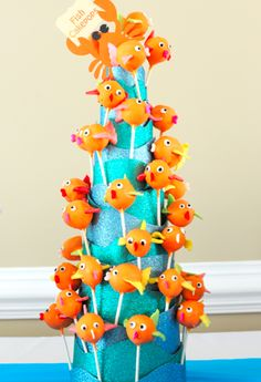 Fish Cake Pops: This is such a great idea for an underwater themed birthday party! I especially like the amazing sparkly wave tower where the orange fish pops are hanging out. This is a great display idea, among a table of other underwater themed sweets.