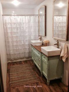 Wood floors, painted light green buffet repurposed into bathroom vanity, white ruffle shower curtain